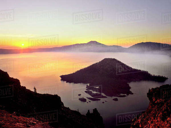 USA, Oregon, Crater Lake National Park. Sunrise over Crater Lake and Wizard Island. Royalty-free stock photo