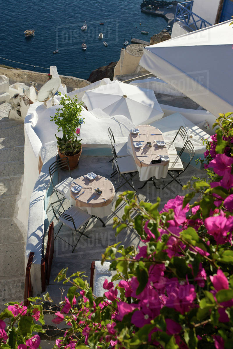 Greece, Santorini, Thira, Oia. Looking Down On Patio Tables Set For Dinner.