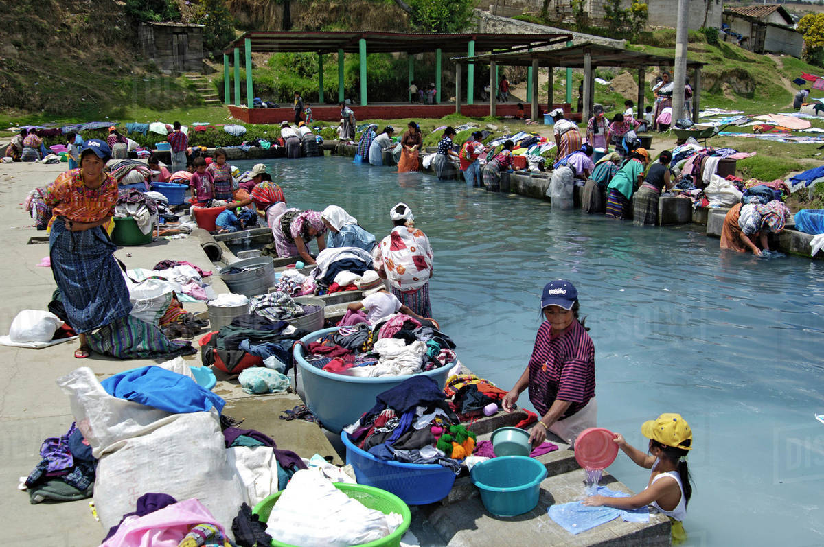 Guatemala Women Standing In Water Washing Clothes By Hand