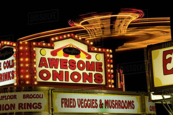 USA, Indiana, Indianapolis. State Fair amusement ride in motion behind lit food booth signs. Royalty-free stock photo
