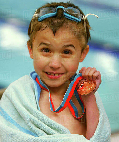 USA, Indiana, Noblesville. A young Special Olympian shows off his first swimming medal. Royalty-free stock photo