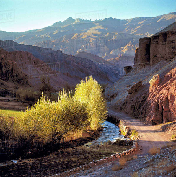Afghanistan, Bamian Valley. A dirt road parallels a stream winding through the Bamian Valley, a World Heritage Site, in Afghanistan. Royalty-free stock photo
