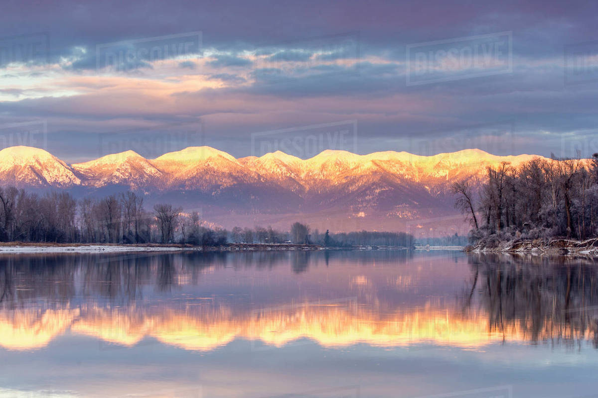 Swan Mountains reflect into the Flathead River at sunset near Kalispell,  Montana, USA stock photo