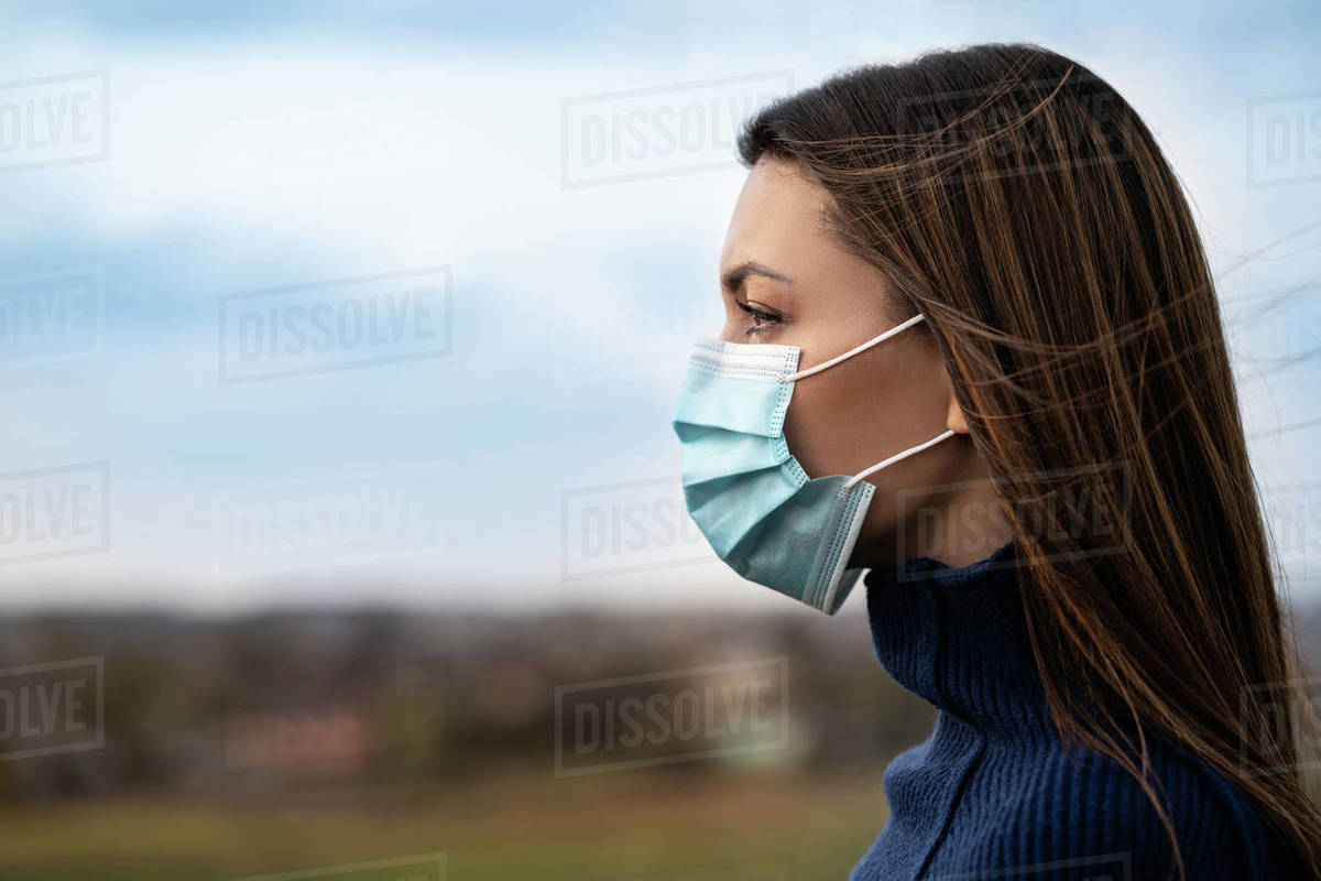The young woman in medical mask standing outside Royalty-free stock photo