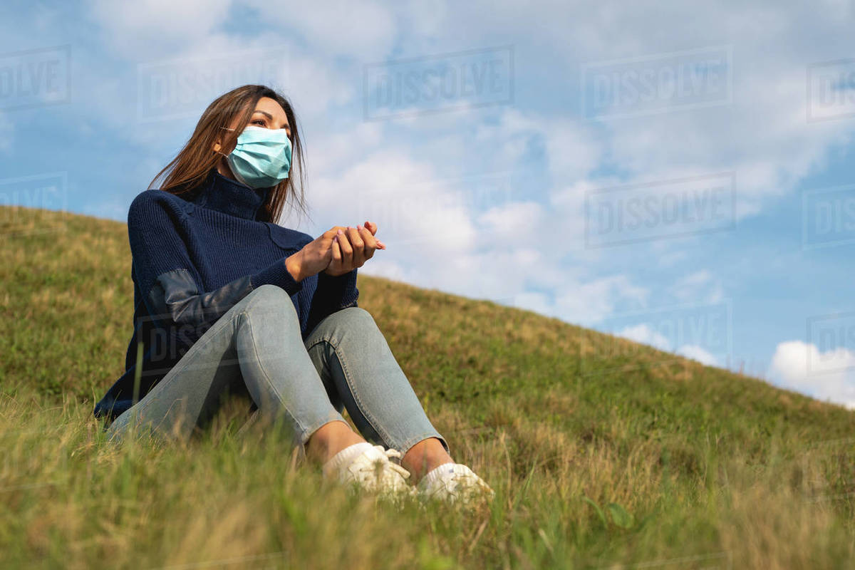 The girl in medical mask sitting on the green grass on the blue sky background  Royalty-free stock photo