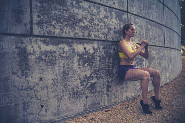 Young woman leaning against wall outdoors, doing squats Royalty-free stock photo