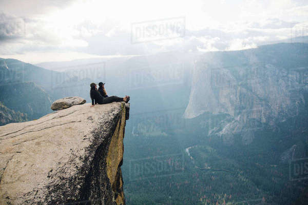 Two young women sitting at top of mountain, overlooking Yosemite National Park, California, USA Royalty-free stock photo