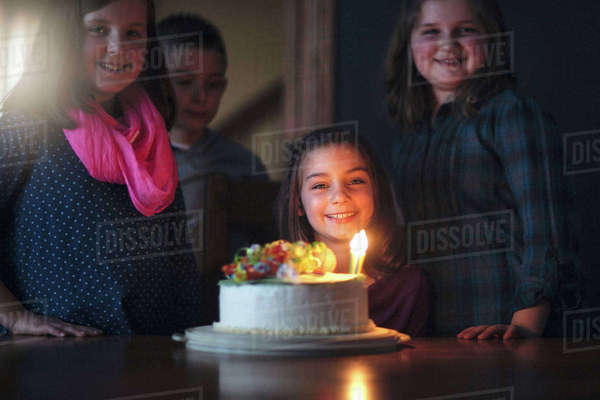 Girl with birthday cake surrounded by friends Royalty-free stock photo