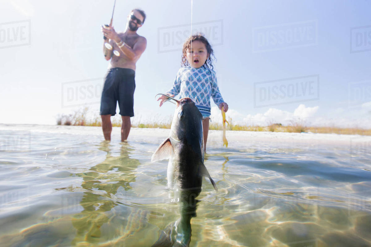 57e29545ff7b5 Daughter watching father catch fish in sea