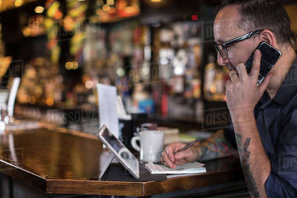 Barman talking on smartphone at public house counter Royalty-free stock photo