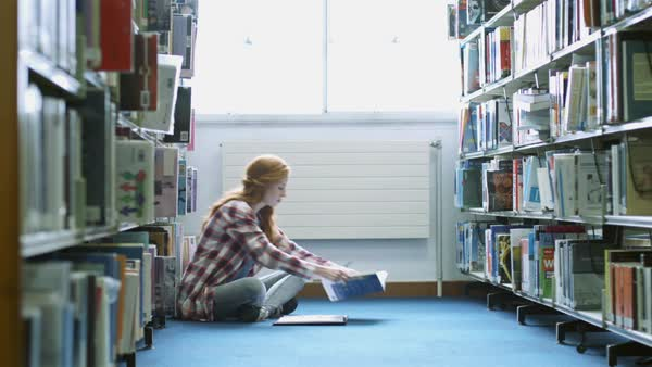 Female student studying on floor in library Royalty-free stock video