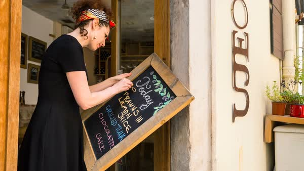 MS Woman writing menu on blackboard Royalty-free stock video