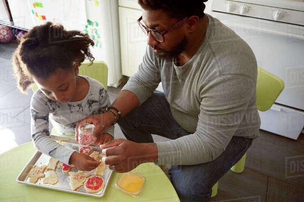 Father and daughter decorating unbaked cookies Royalty-free stock photo