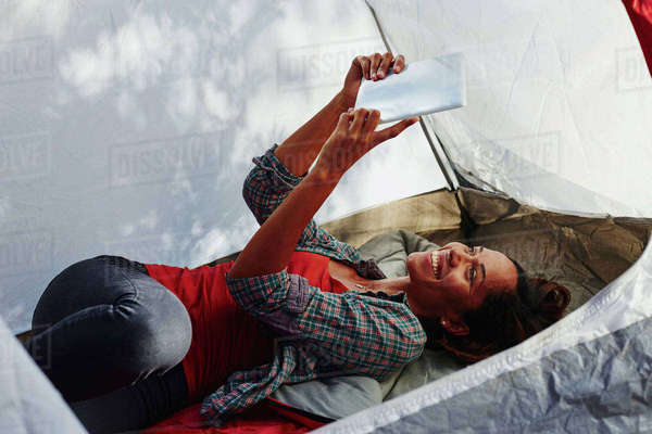 Mid adult woman camping, lying in tent taking digital tablet selfie Royalty-free stock photo