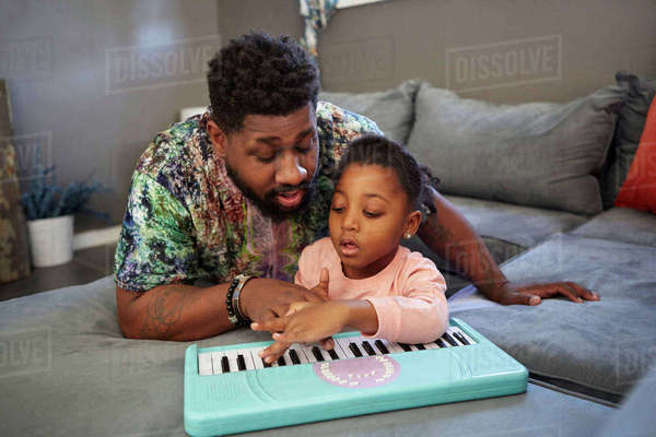 Girl lying on sofa with father playing toy keyboard Royalty-free stock photo