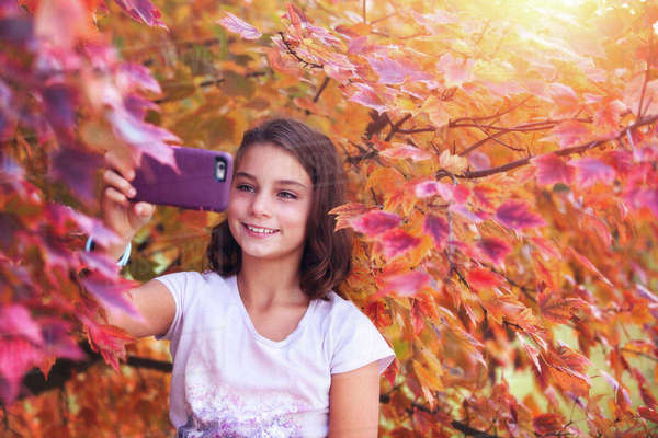 Young girl in rural setting, taking selfie with smartphone Royalty-free stock photo