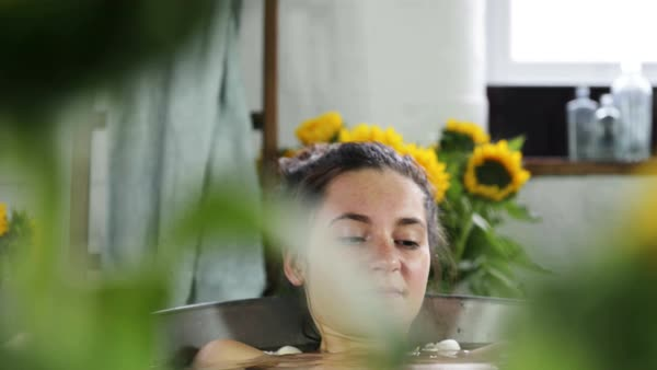 Young woman lying down in bathtub surrounded with sunflowers Royalty-free stock video