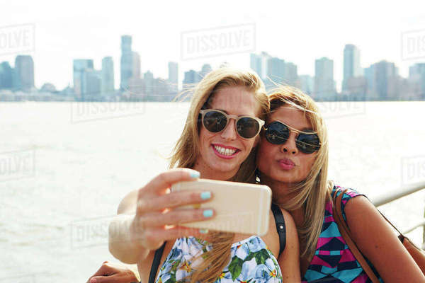 Two women taking smartphone selfie on waterfront with skyline, New York, USA Royalty-free stock photo