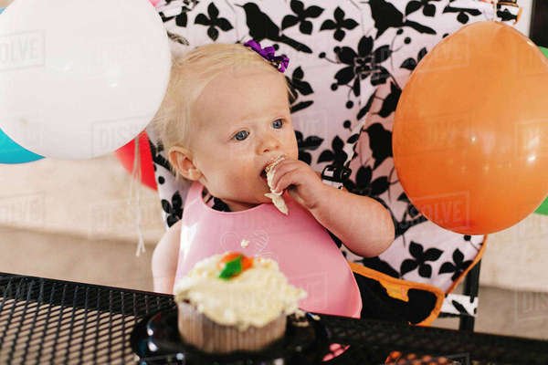Baby girl sitting in high chair, eating birthday cake Royalty-free stock photo
