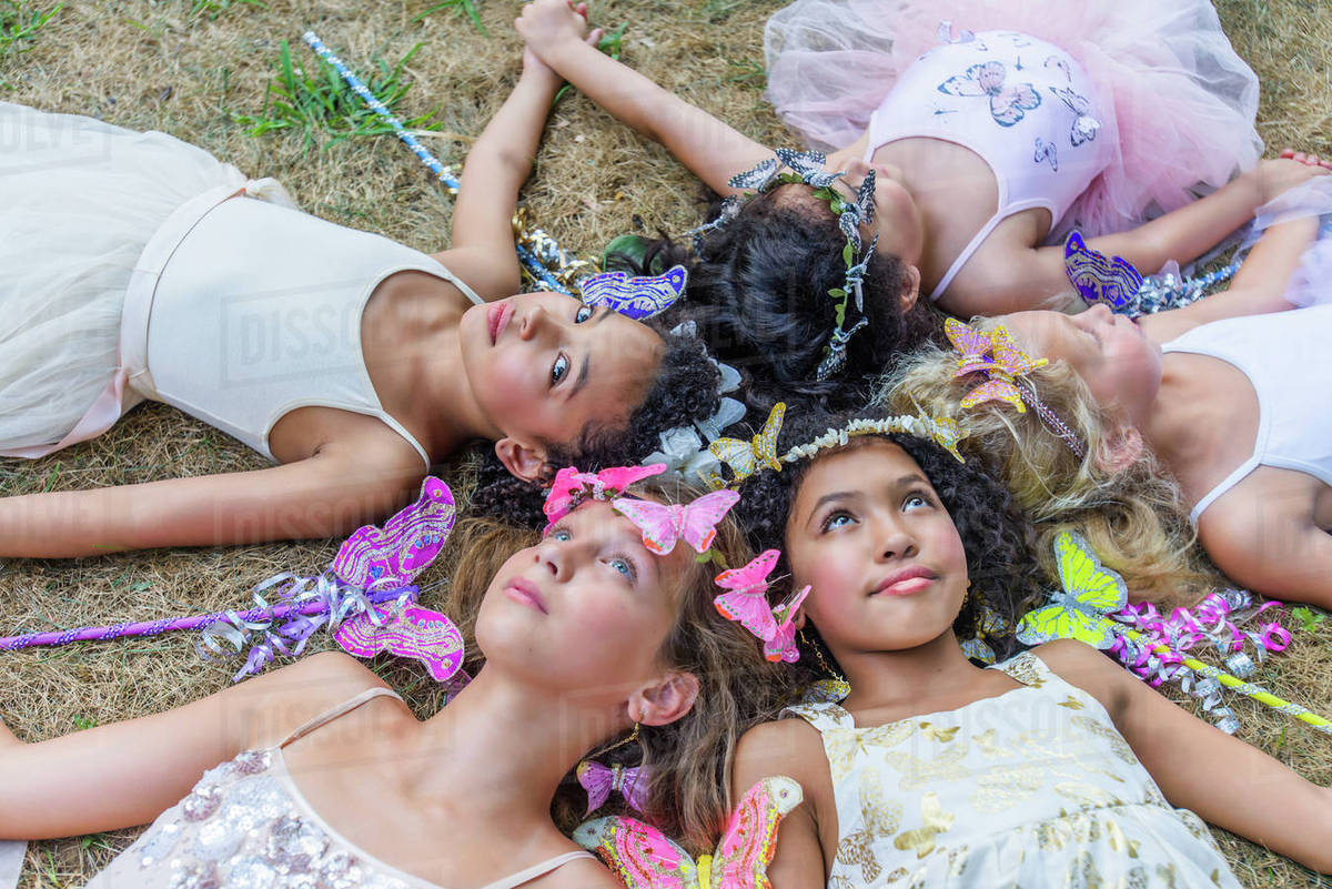 Group of young girls dressed as fairies, lying in circle, heads together Royalty-free stock photo