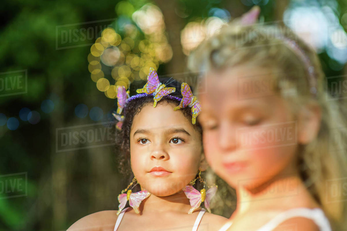 Two young girls, outdoors, wearing butterflies in hair Royalty-free stock photo