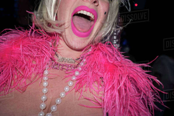 Mid adult woman in party clothes, with pink feather boa and pink lipstick, mid section Royalty-free stock photo