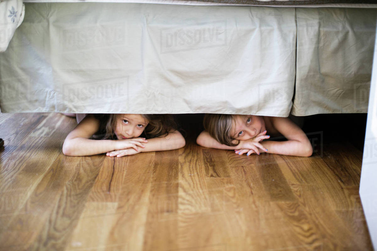 Boy And Girl Hiding Under Bed Stock Photo Dissolve