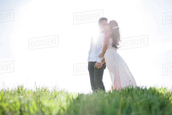 Romantic couple kissing on sunlit grassy hill Royalty-free stock photo