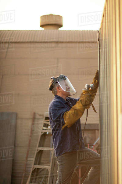 Welder using power tool on shipping container Royalty-free stock photo