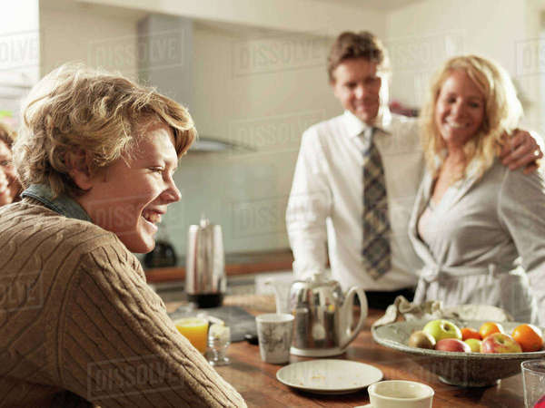 Teenage son sitting at kitchen table with parents in background Royalty-free stock photo