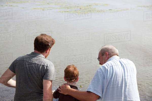 Boy at river with father and grandfather Royalty-free stock photo