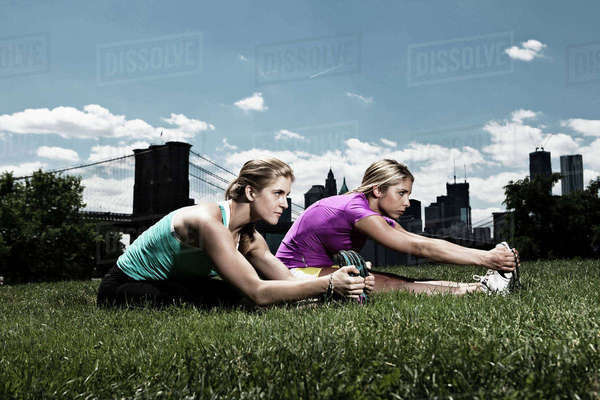 Two women stretching in park Royalty-free stock photo