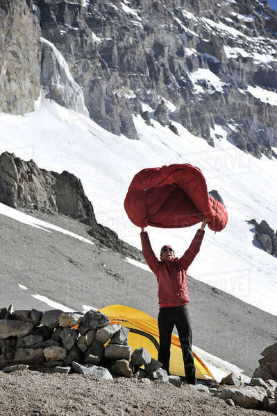 Woman shakes her sleeping bag at Camp One on Aconcagua in the Andes Mountains, Mendoza Province, Argentina Royalty-free stock photo