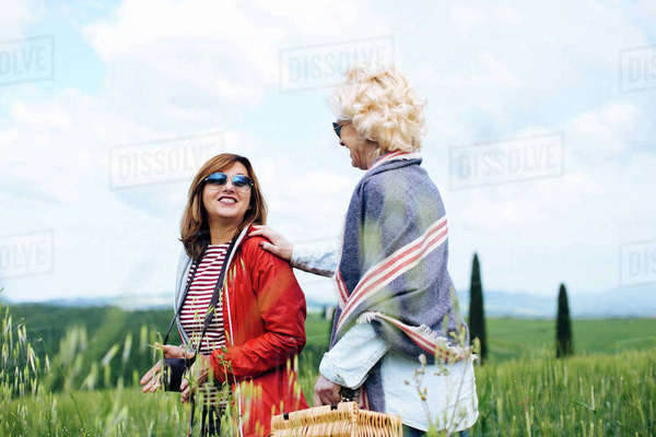 Two mature women with picnic basket in wheatfield, Tuscany, Italy Royalty-free stock photo