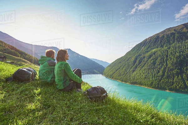 Young couple sitting  looking out over Vernagt reservoir and Finailhof farmhouse, Val Senales, South Tyrol, Italy Royalty-free stock photo