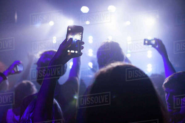 Group of friends watching and taking photograph of performer in club Royalty-free stock photo