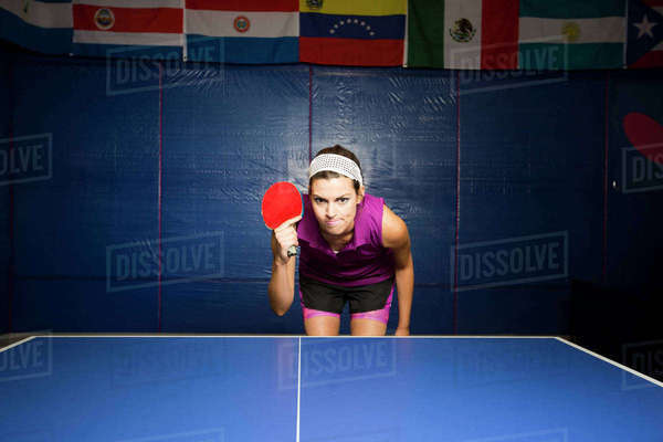 Table tennis player with bat bending forward at table Royalty-free stock photo