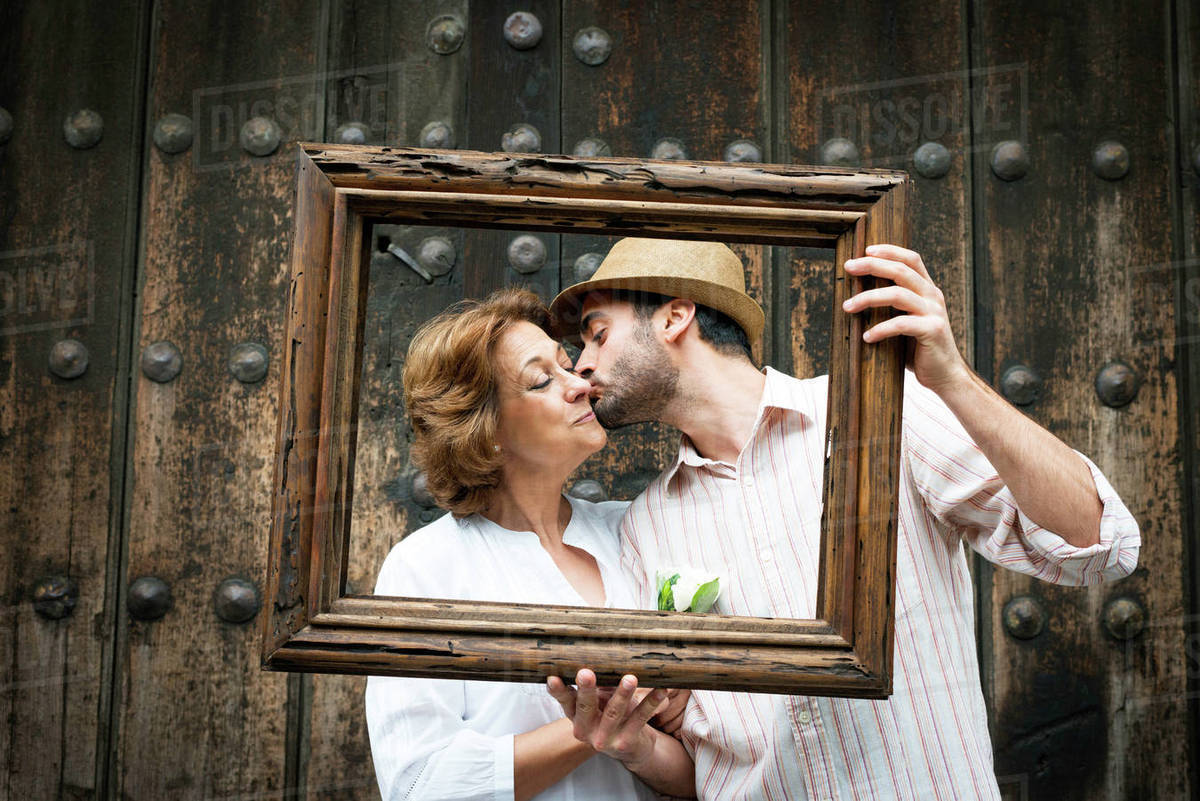 Portrait Of Adult Son Kissing Mother On Cheek Holding Wooden Frame