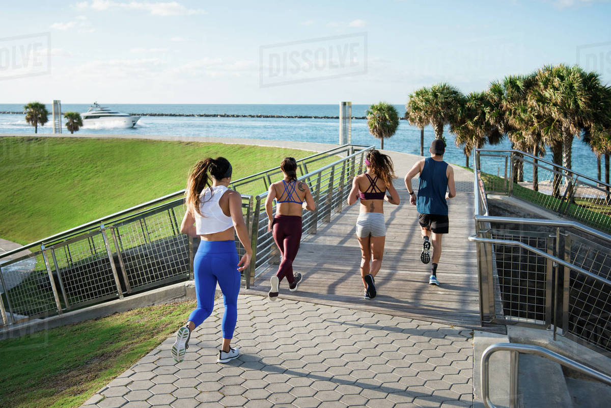 Three Women Running With Personal Trainer Rear View South Point Park Miami Beach Florida Usa
