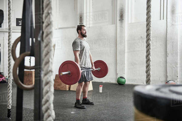 Man lifting barbell in cross training gym Royalty-free stock photo