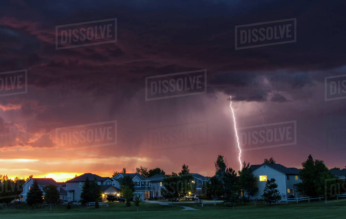 Forked lightning in orange sky over urban area, Aurora, Colorado, United  States, North America stock photo