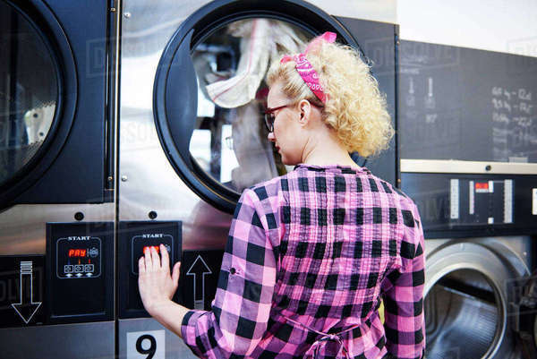 Woman pressing washing machine buttons at laundrette Royalty-free stock photo