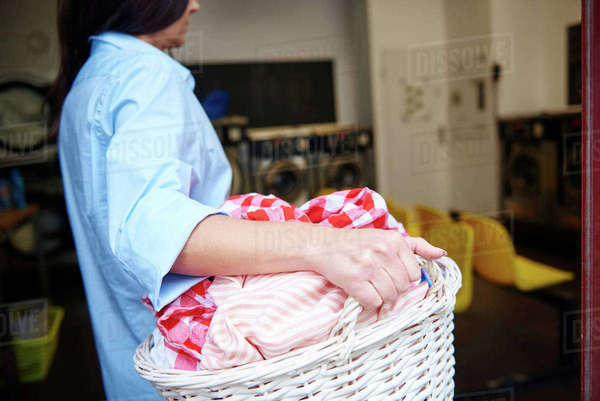Woman carrying laundry basket in laundrette Royalty-free stock photo