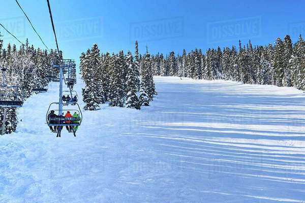 Rear view of skiers on ski lift moving up snow covered landscape, Aspen, Colorado, USA Royalty-free stock photo