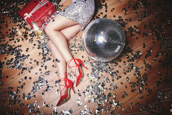 Woman lying on floor at party, surrounded by glitter, champagne bottle and disco ball, overhead view Royalty-free stock photo