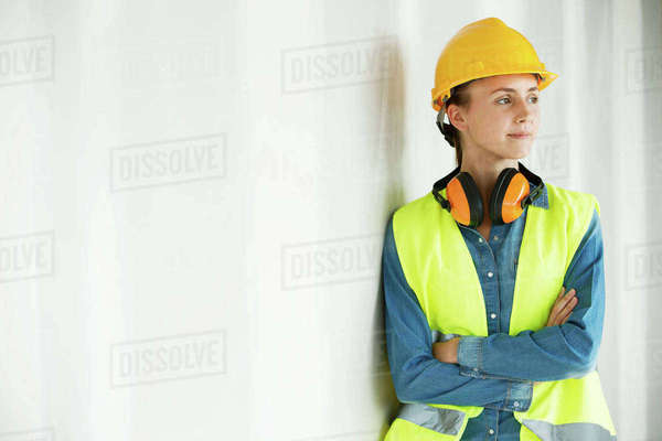 Young woman, wearing hi vis vest and hard hat, leaning against wall, arms folded Royalty-free stock photo
