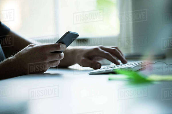 Hand of male designer using smartphone and typing on keyboard at creative studio  desk Royalty-free stock photo