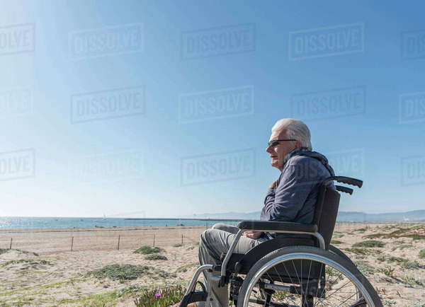 Senior man in wheelchair looking out from dunes, Playa del Ray, California, USA Royalty-free stock photo