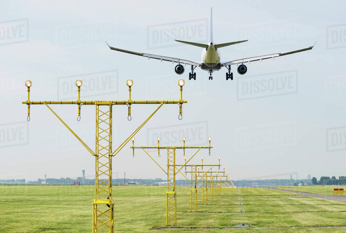 Airplane landing by runway landing lights, Schiphol, North Holland,  Netherlands, Europe stock photo