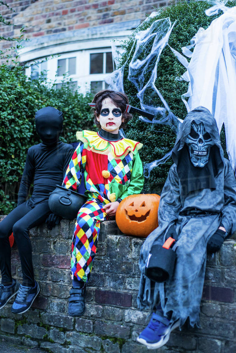 portrait of three boys in halloween costumes, sitting on wall